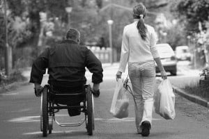 A black and white view from behind of a man in a black jacket pushing a wheelchair next to a woman in white who is walking and carrying grocery bags.